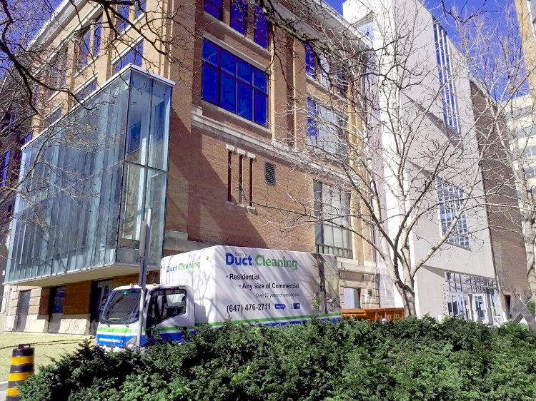 Truck is parked at the side of the University building while the suction and compressor hoses run up to each of the floors - Sem's Duct Cleaning Toronto
